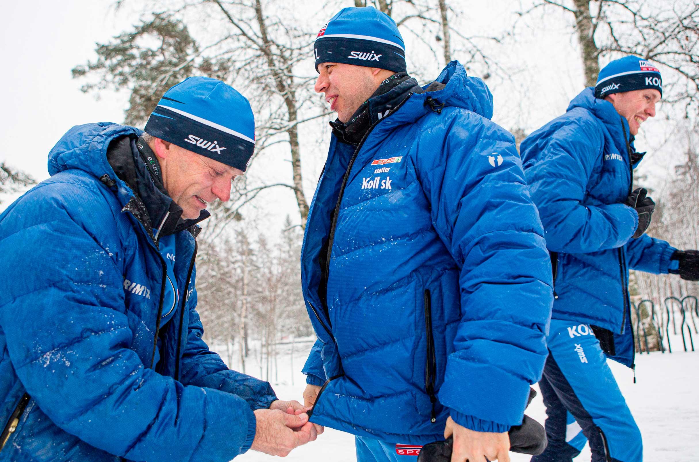 Bilde av Kjetil Ørbeck som knepper igjen jakken til en utøver. I bakgrunnen går en tredjeperson. De er alle ikledd blå jakker og luer, og det er snø på bakken.