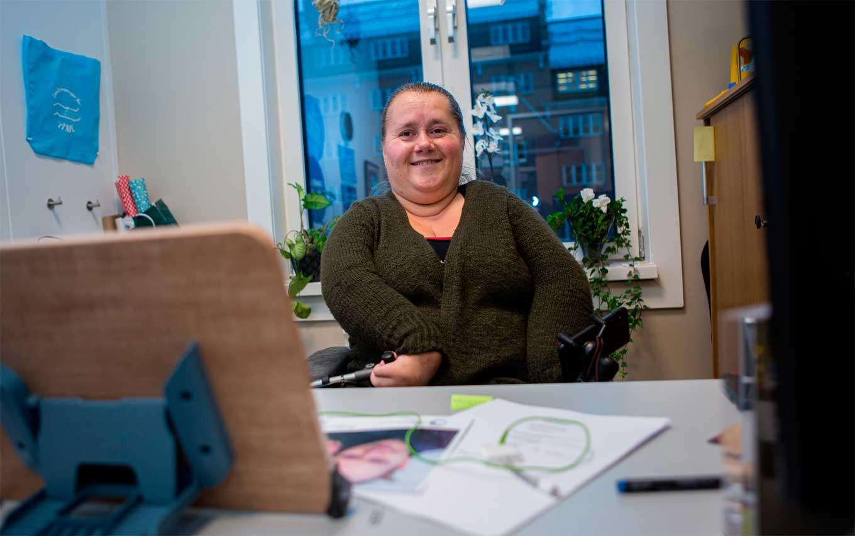 Bilde av Monica Haugen bak et skrivebord på kontoret sitt. Bak henne er et vindu og et bygg skimtes utenfor.