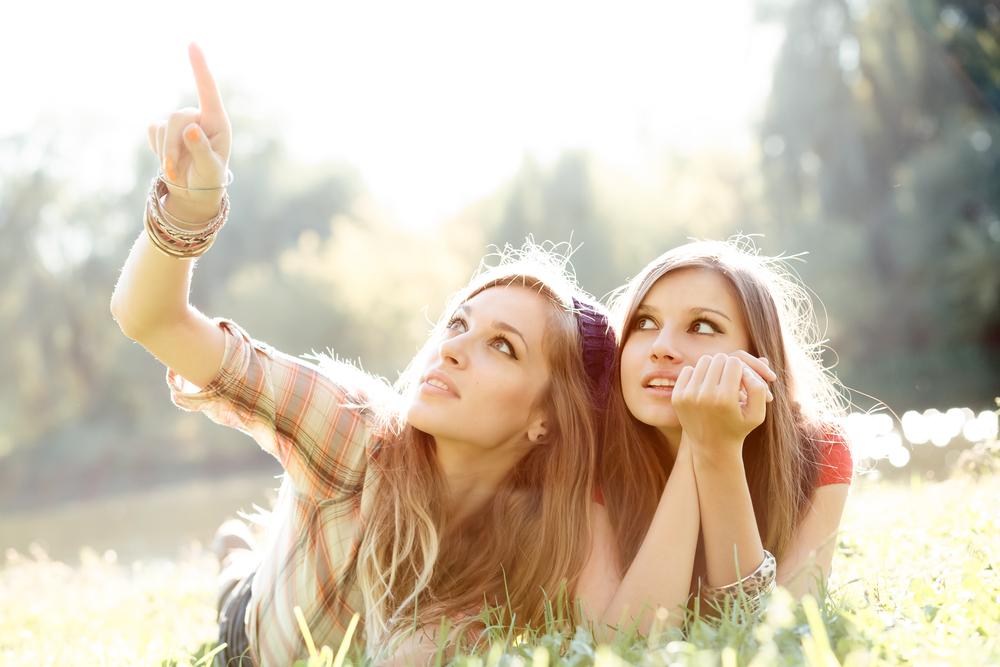 Bilde av to kvinner som ligger på magen i en eng. Kvinnen til venstre peker opp mot noe utenfor bildet, mens den andre kvinnen kikker i samme retning. I bakgrunnen skimtes trær.