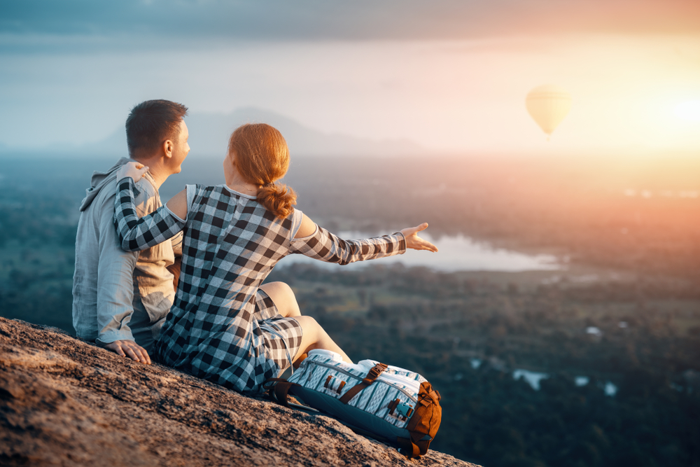 Bilde av en mann og en kvinne som sitter på en fjellknaus. Kvinnen har den ene hånden på mannens skulder mens den andre hånden holdes ut mot landskapet. Hun har en ryggsekk ved siden av seg. Foran dem skimtes trær og en innsjø.
