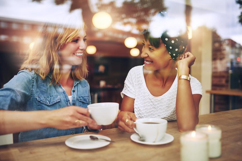 Bilde av to kvinner på en cafe. De kikker smilende mot hverandre. Kvinnen til venstre holder opp en kaffekopp. Bildet er tatt gjennom et vindu.