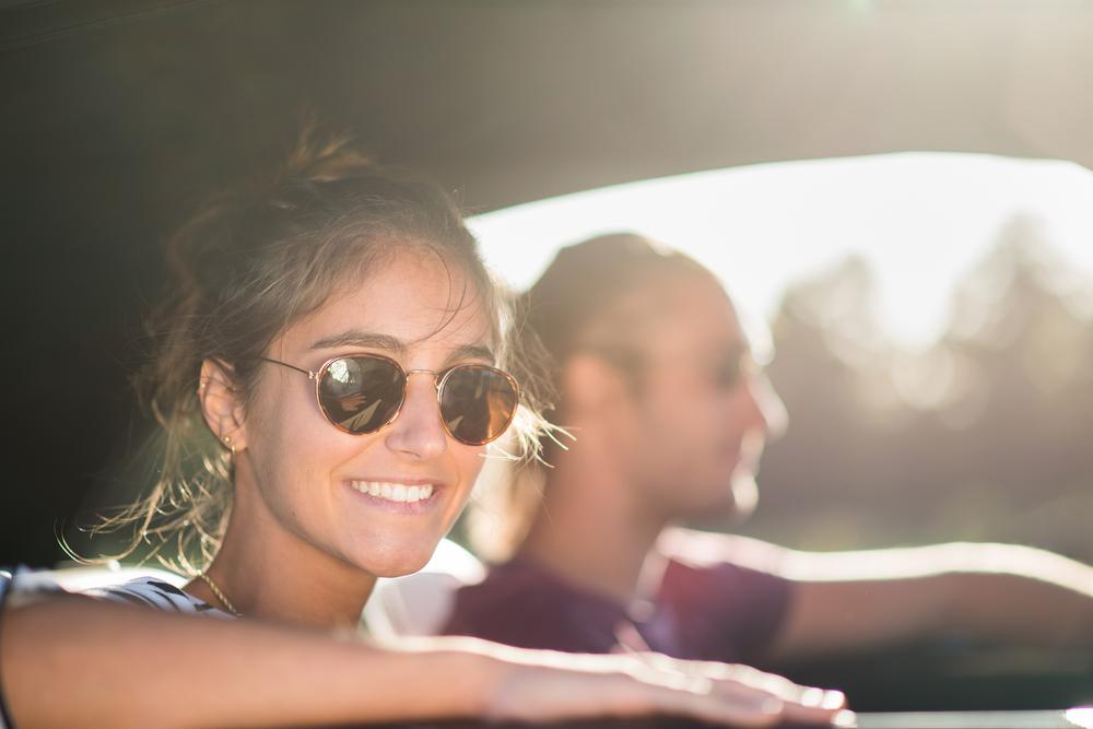 Bilde av en kvinne med solbriller som kikker smilende ut av et bilvindu. I bakgrunnen kan man skimte omrisset av en mann.