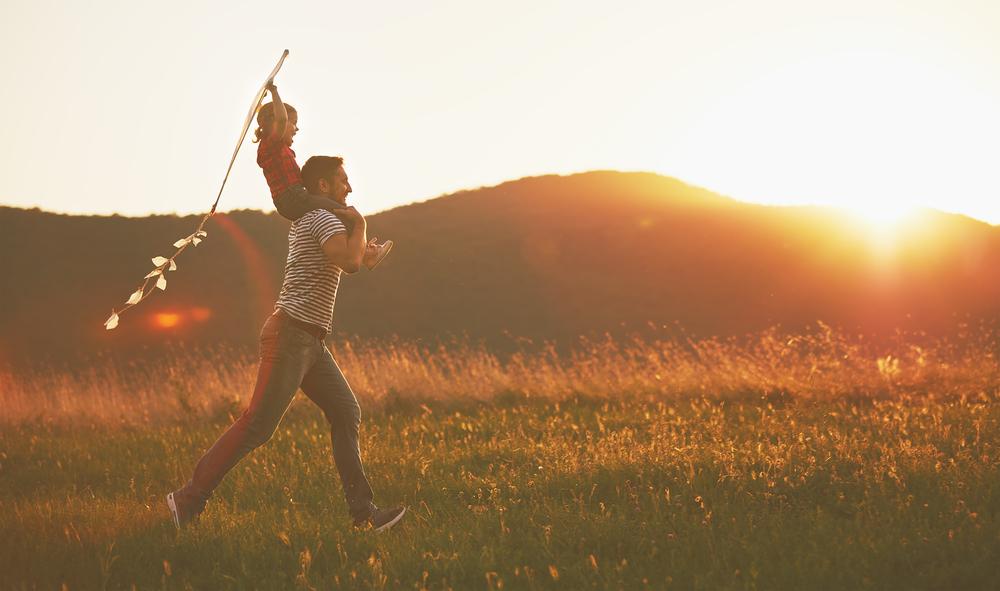 Bilde av en voksen mann og et barn som løper over en eng. Mannen har barnet på skuldrene og barnet har en kvist i hendene.