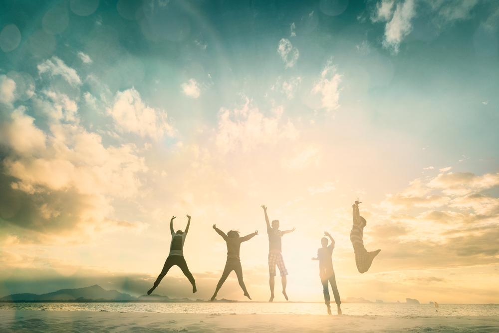 Bilde av fem personer som hopper opp i lufta på en strand. Det er ikke mulig å se ansiktene deres. I bakgrunnen skimtes hav og fjellformasjoner.