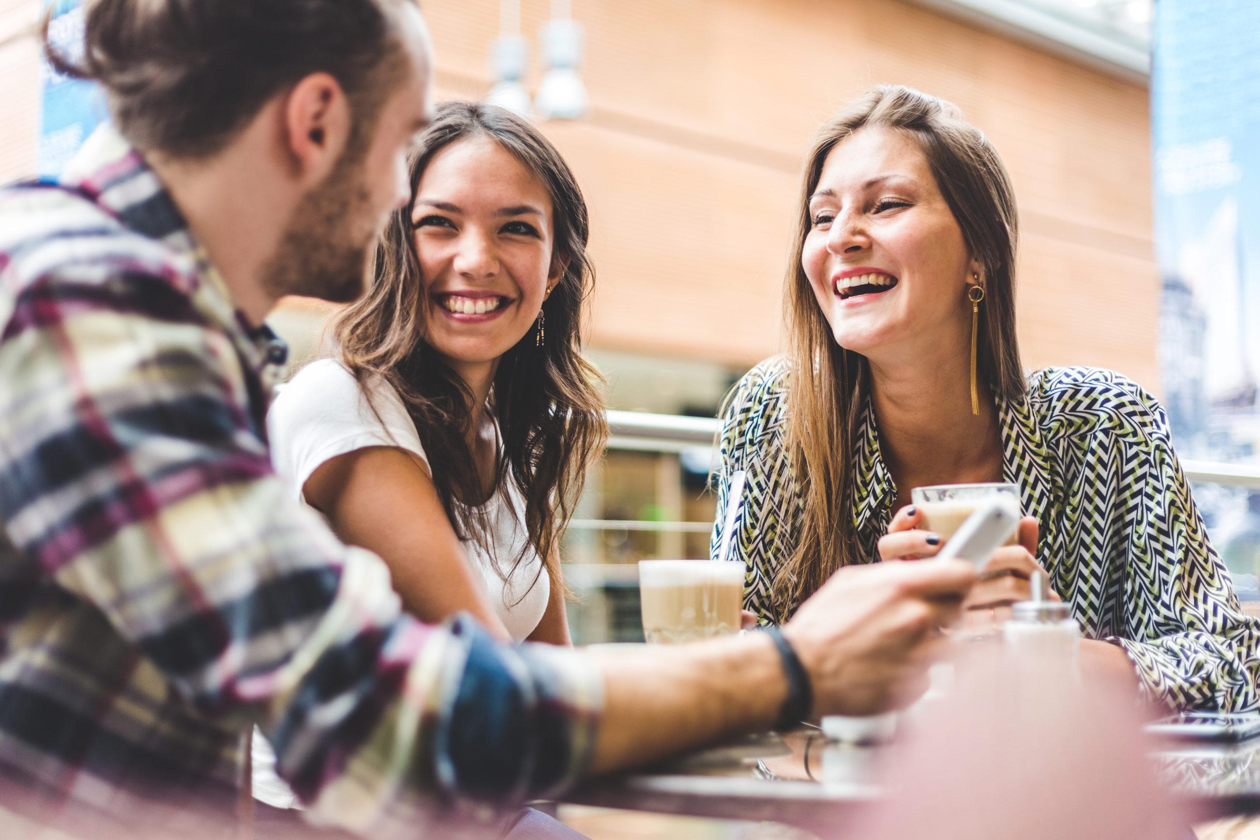 Bilde av en mann og to kvinner rundt et bord. De to kvinnene smiler bredt mens de ser bort på mannen. De ser ut til å ha et kaffemøte.