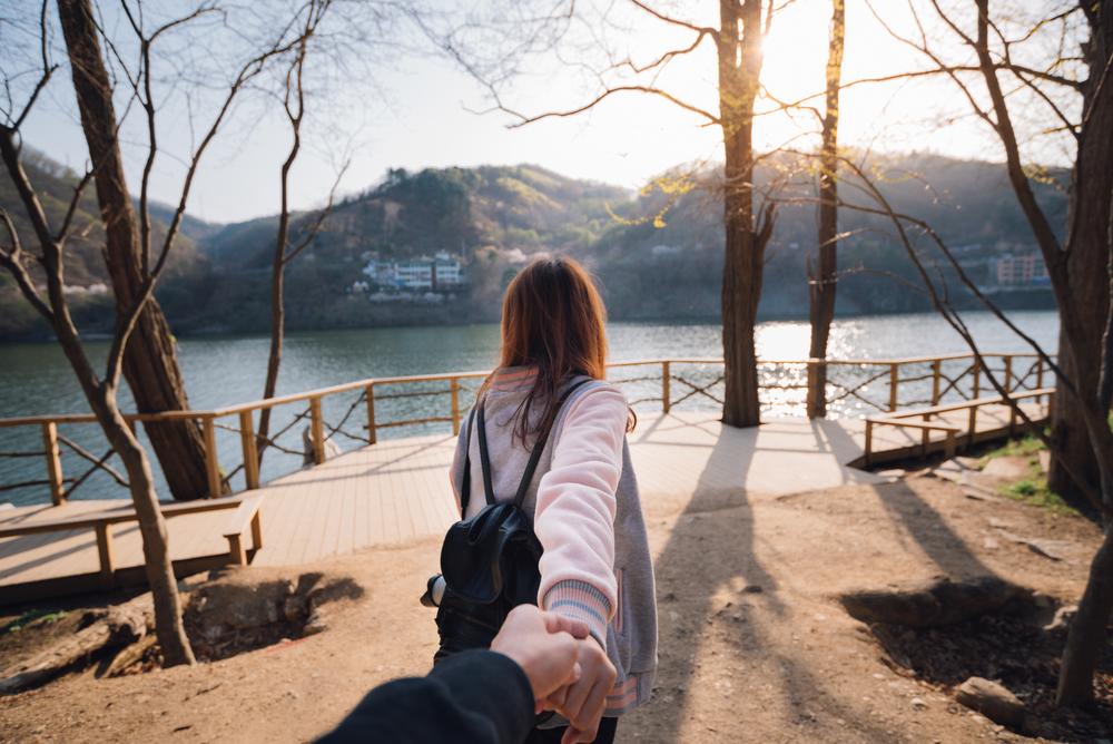 Bilde av en kvinne som har ryggen til kameraet. Hun holder hånden til en person utenfor bildet. Kvinnen har på seg en ryggsekk og er på vei mot en gåsti langs vannet.
