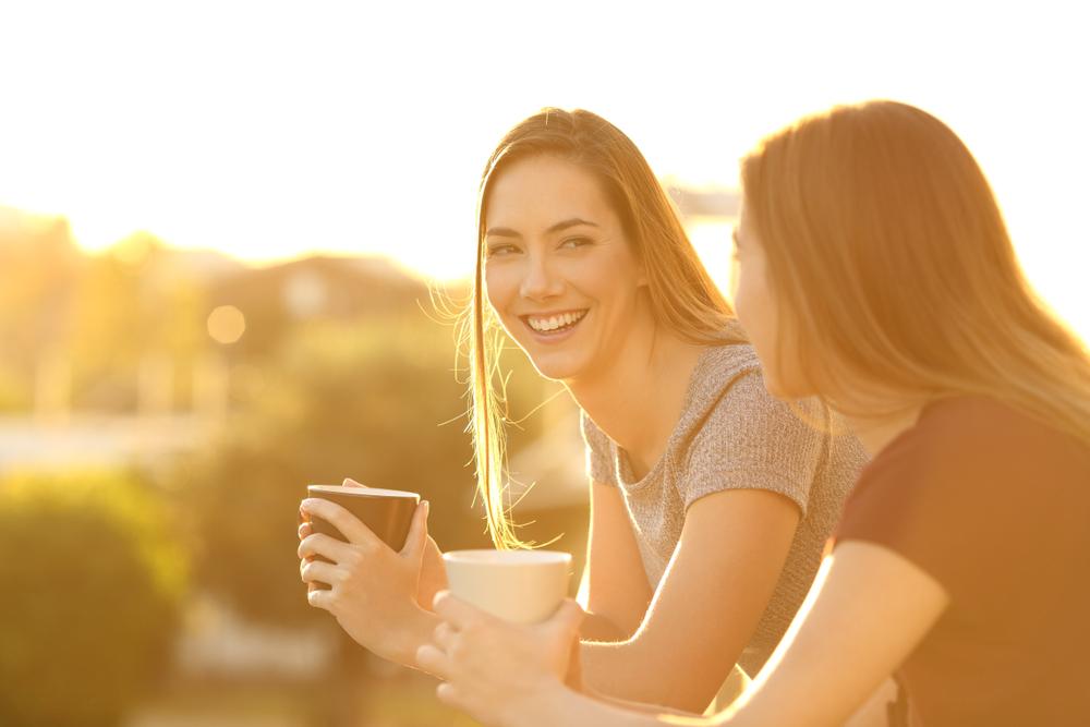 Bilde av to kvinner. Kvinnen til venstre kikker smilende bort på den andre kvinnen, som kikker mot henne og dermed bort fra kameraet. De holder begge en kopp i hendene. Bildet har et gult filter, slik at det virker som om det er ved soloppgang eller solnedgang.