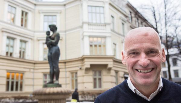 Bilde av en smilende Geir Lippestad. Han kikker inn i kameraet. I bakgrunnen skimtes en statue og et gult bygg i Oslo.
