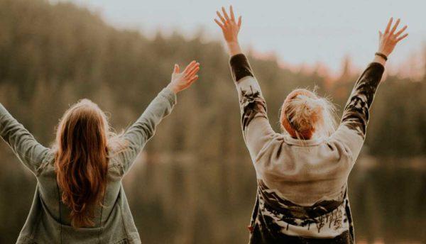 Bilde av to kvinner som begge holder armene opp i V-formasjon. De har ryggen mot kameraet. Foran dem kan det skimtes en innsjø og trær.