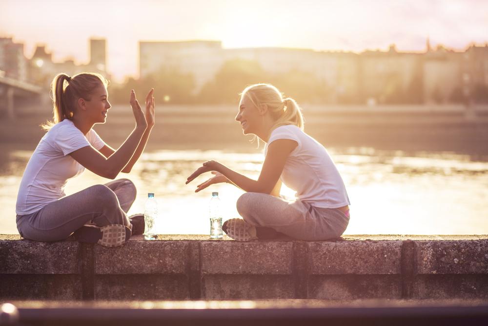 Bilde av to kvinner som sitter på en murvegg. De er begge ikledd hvite t-skjorter og treningsbukser. Kvinnen til venstre holder opp hendene mens kvinnen til høye holder ut hendene, som ved en klappelek. I bakgrunnen skimtes vann og bygninger.