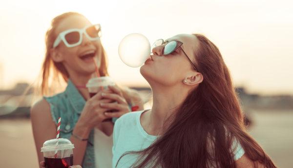 Bilde av to kvinner. Kvinnen i forgrunnen har en plastkopp i hånden og blåser en tyggisboble. Kvinnen i bakgrunnen holder rundt en plastkopp mens hun smiler bredt mot tyggisboblen.