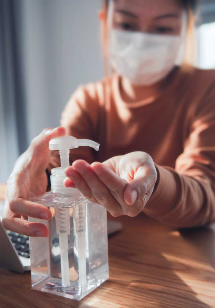 Nærbilde av en kvinne med munnbind som spriter hånden med desinfiserende middel.