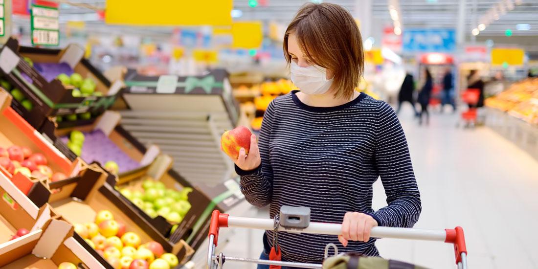 Bilde av en kvinne iført munnbind i fruktavdelingen i en matvarebutikk. Hun hviler den ene hånden på handlevognen og i den andre hånden holder hun et eple.
